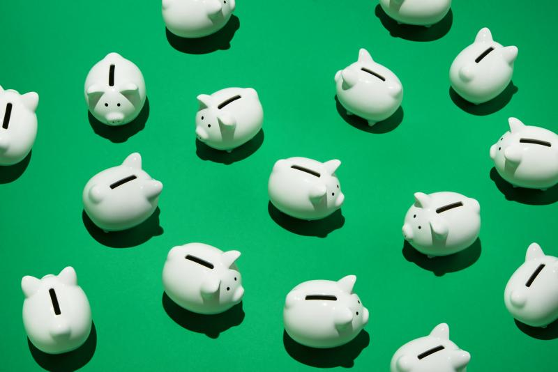 manny white piggy banks on a green backdrop