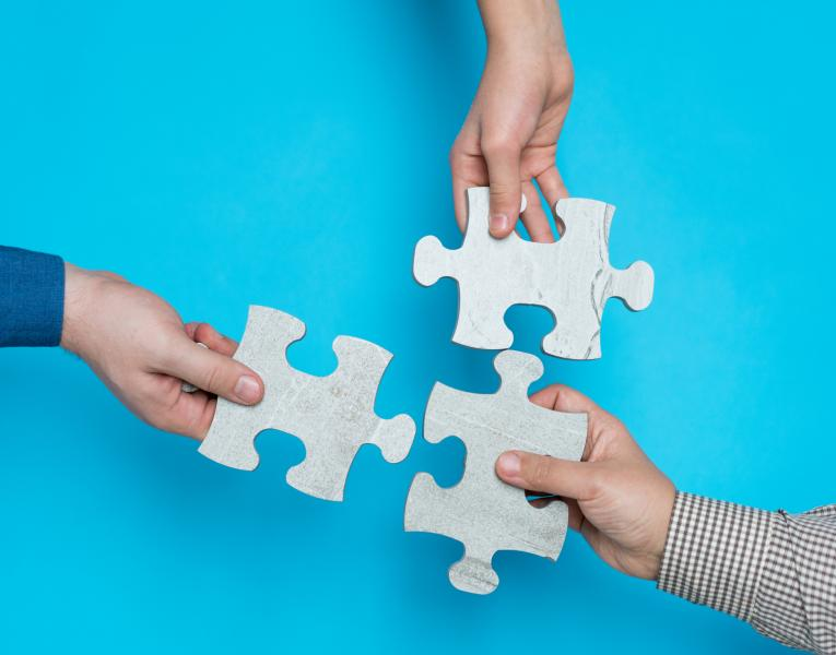 three people holding puzzle pieces, putting them together, blue background