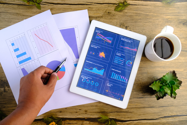Electronic tablet with graphs, charts, metrics, etc. on top of papers with metrics on wooden background next to plant and coffee