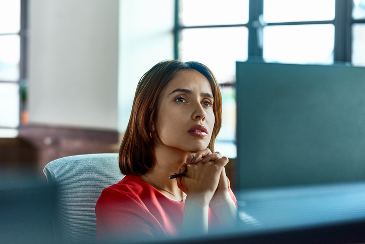 woman at desk staring into distance