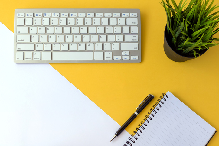 Yellow and white background with keyboard, notebook and pen, and plant