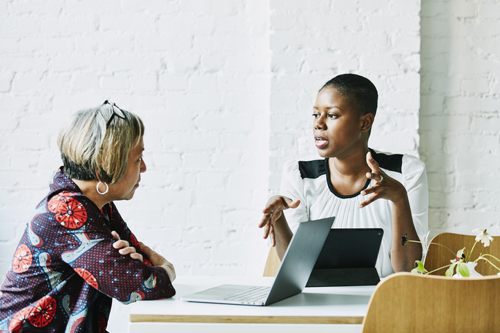 one woman advising another at a business setting
