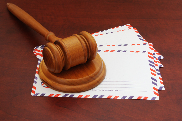 Judge's gavel on top of envelopes