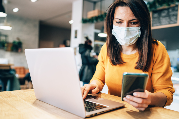 Woman with medical mask on looking at phone and laptop