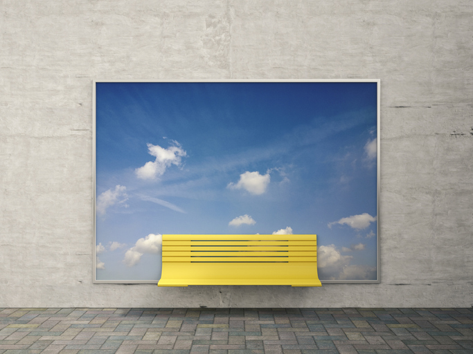 Picture of a bench in front of a blue sky advertisement.