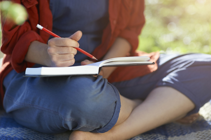 Person sitting and writing in a journal