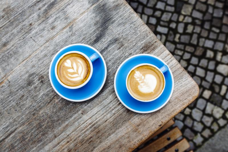 Two latte cups on blue plates sitting on a wooden table.