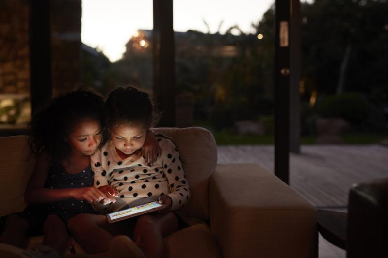 Two girls curled up on the couch looking at an ipad in the dark