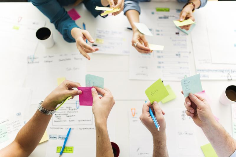 Picture of hands holding post-it notes brainstorming a strategy