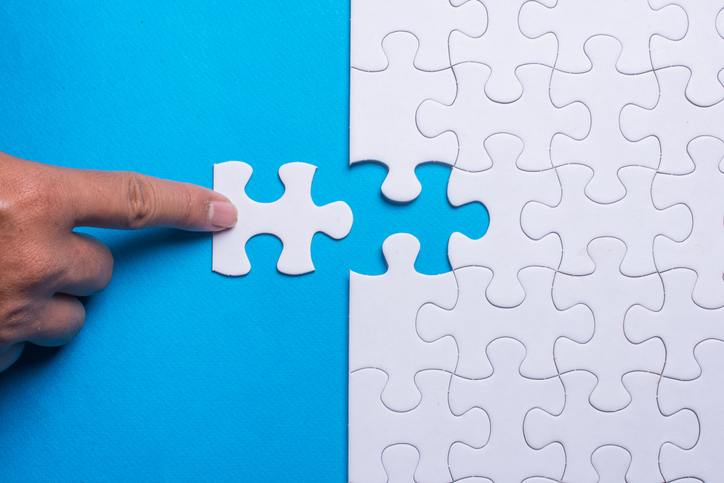 Picture of a finger adding the last missing puzzle piece to a otherwise completed puzzle.