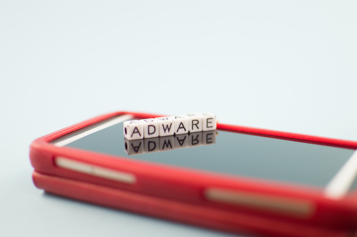 "The word ""Adware"" spelled out in blocks sitting on top of a mobile phone."