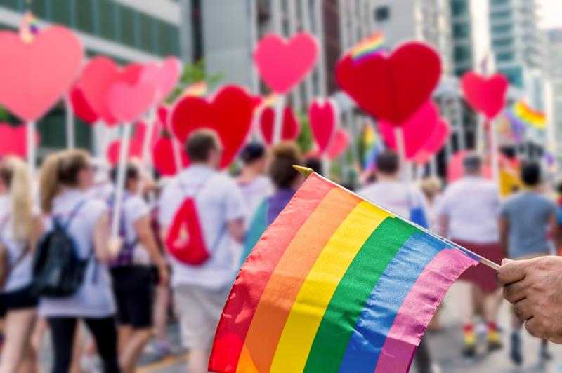 LGBTQ pride parade. Picture of a hand holding a pride flag in front of a group of marchers holding hearts.