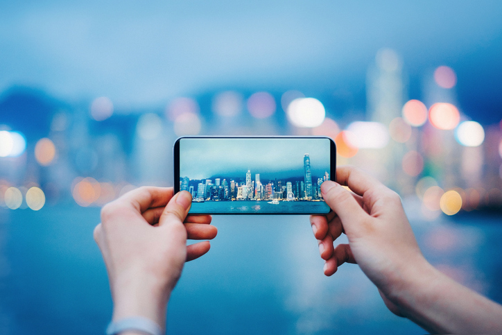 Picture of hands holding up an iPhone taking a picture of a city skyline on the water.