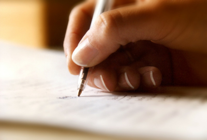 a hand writes in a notebook