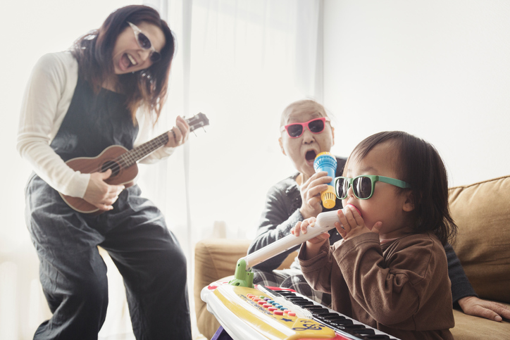 Family singing and playing various instruments in a living room wearing sunglasses.