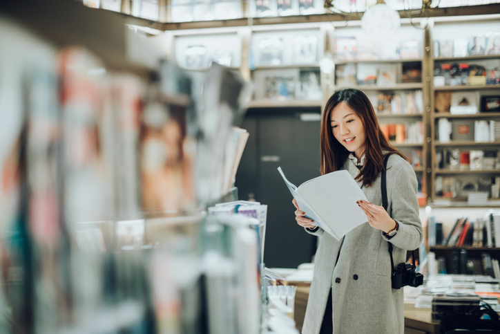 Professional female photographer reading books in book store for inspiration