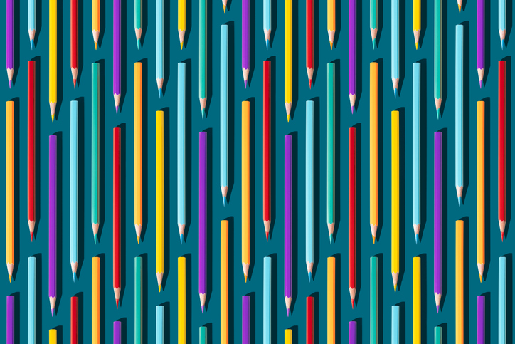 Colored pencils vertical, on dark turquoise background