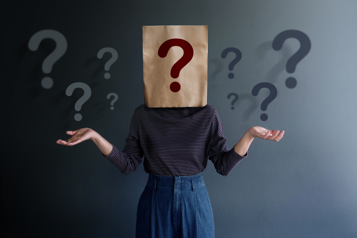 Picture of a woman with a paper bad over her head with a question