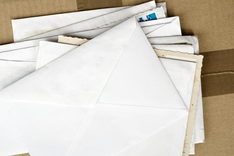 Several pieces of unaddressed mail/envelopes on a cardboard box
