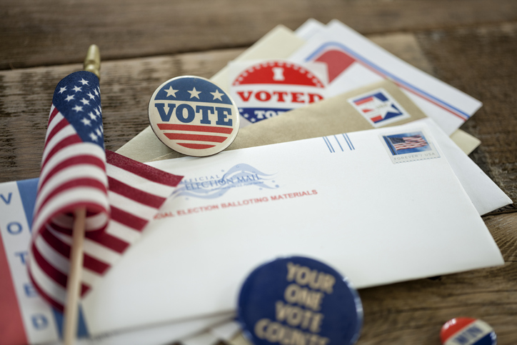 "Pile of mail-in voting envelopes and ""I Voted"" stickers and an American flag"