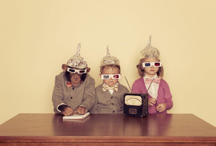 Monkey and kids wearing tin foil hats and 3D movie glasses with radio and notepad