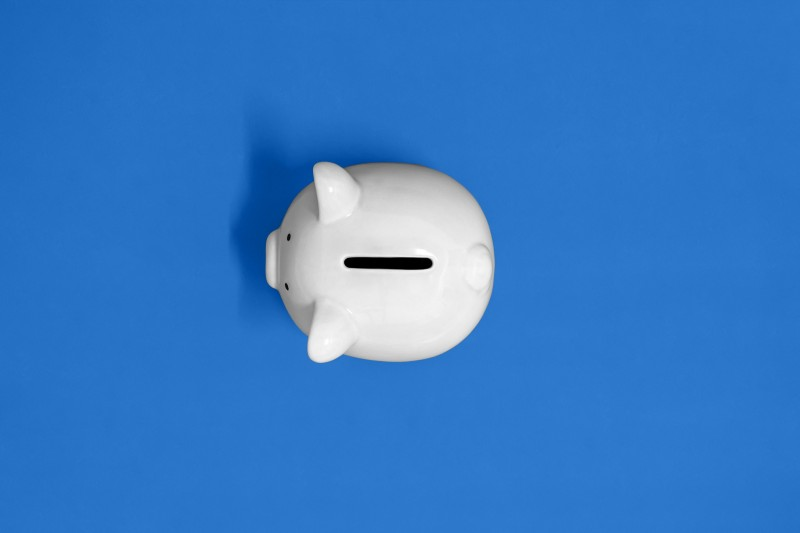 white piggy bank facing left with a blue background
