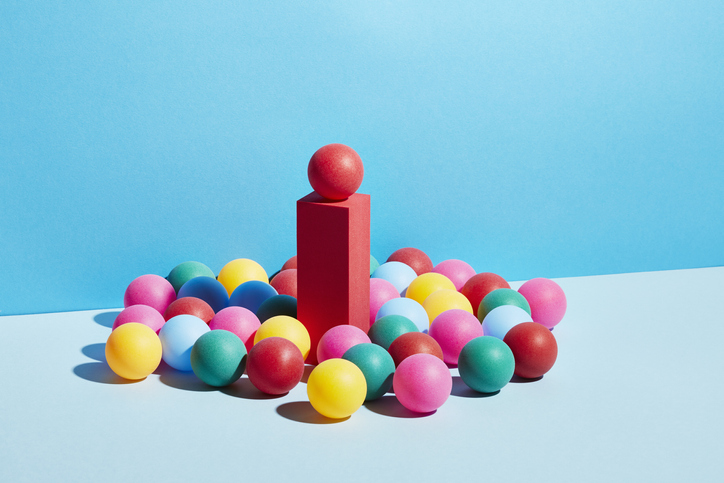 A bunch of colorful balls surrounding a red block with a ball on top of it.