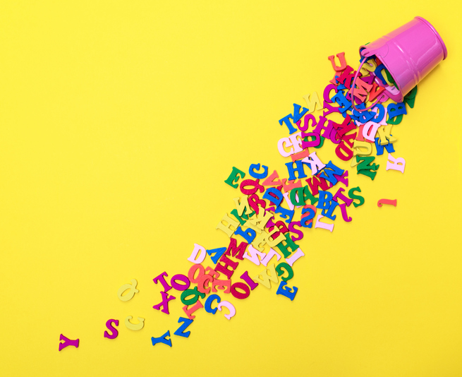 Bright yellow background with a pink cup in the top right corner that has letters falling out of it.