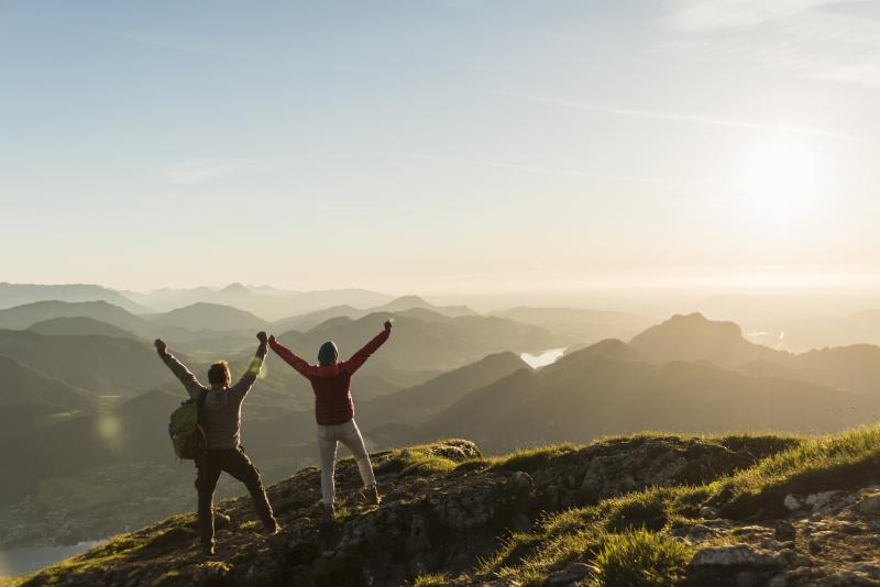 two people at the top of a mountain with their hands up in excitement for their success