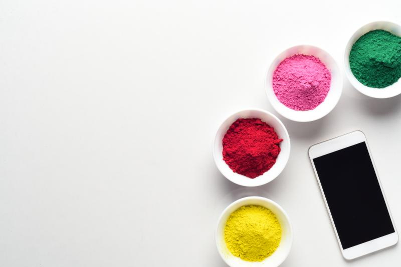 iPhone surrounded by holi colored bowls to symbolize choices.