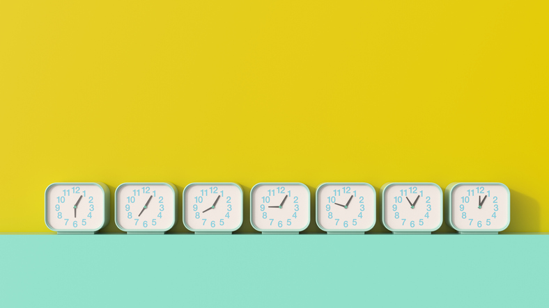 7 clocks showing different times on a aquamarine shelf in front of a mustard yellow backdrop.
