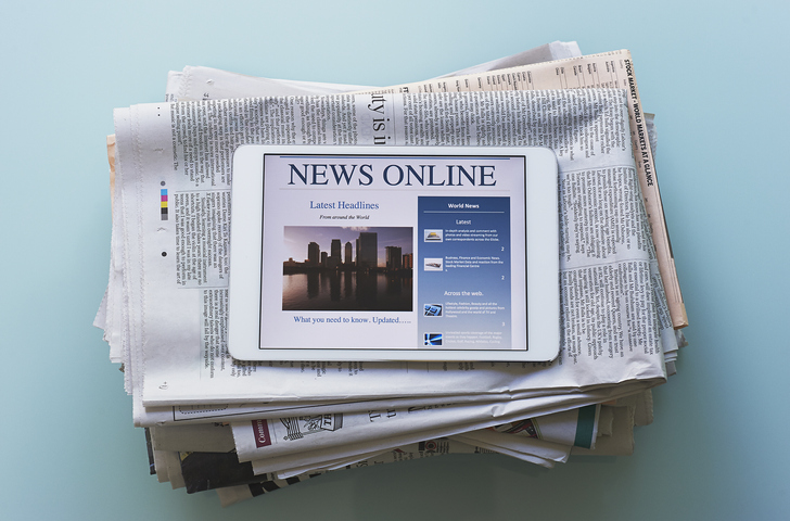 newspaper folded up with a tablet on top of it. Backdrop is light blue.