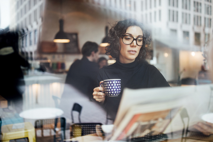 White woman with short hair and glasses sitting in a coffee shop looking at a newspaper with a cup of coffee in her hand.