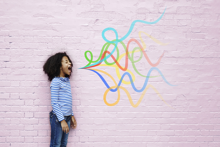 Girl in front of pink brick wall with colorful chalk lines drawn -storytelling for campaign communications.