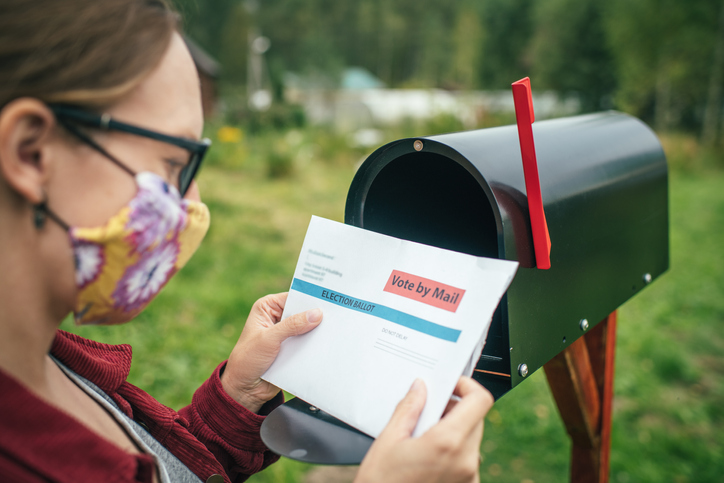 Woman looking at mail in ballot by a mail box