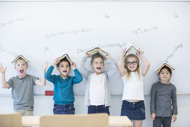 5 children standing against a white board with books on their heads.