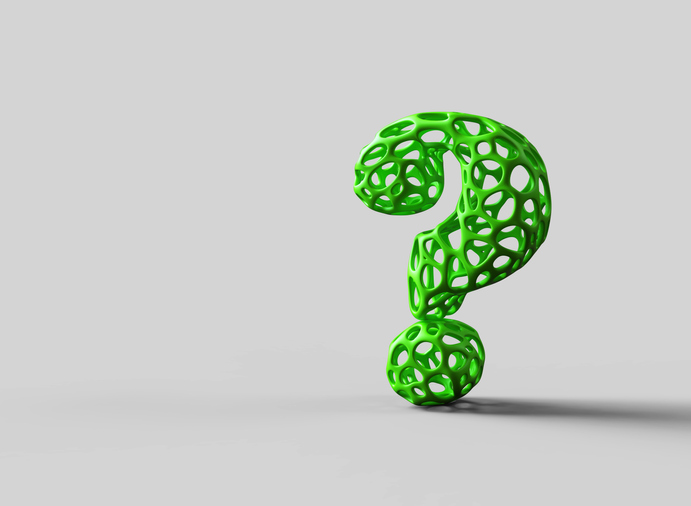 Green question mark made out of rubber with holes on a gray backdrop