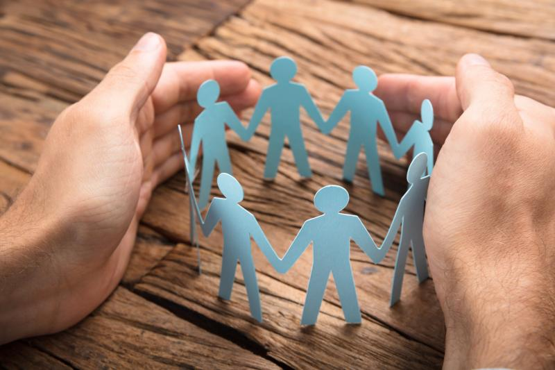 Hands holding a boundary around the paper cut outs of people in a circle